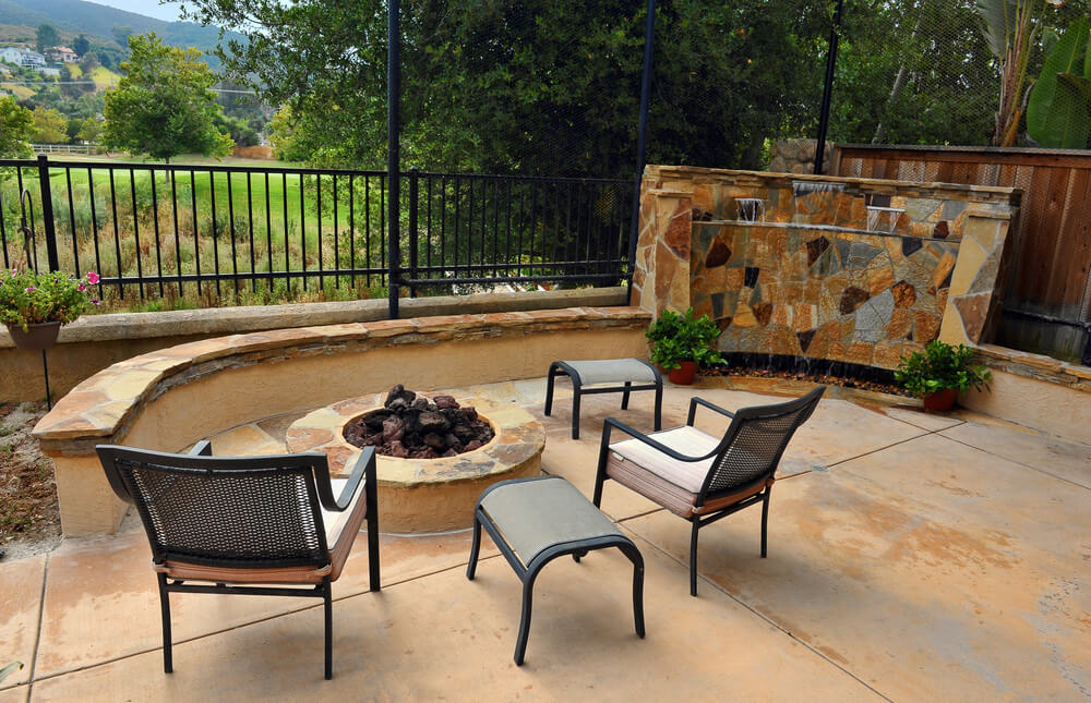 This cozy patio space features raised fire pit and furniture set standing next to flagstone waterfall piece on right.
