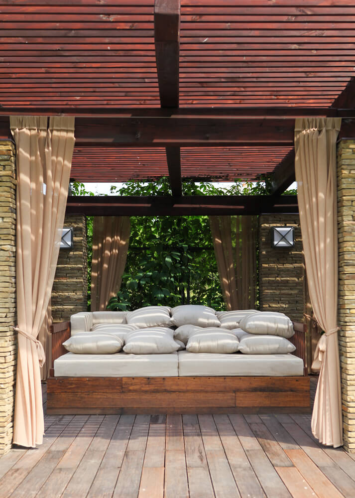 Natural, weathered deck supports rich wood day bed with abundant white cushions, beneath slatted wood roof and brick pillars.