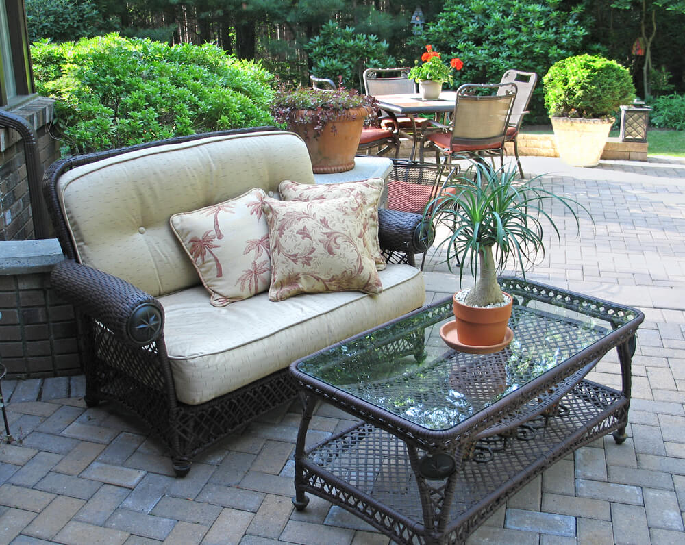 Dark brick patio extends from brick home, with dark wicker and glass coffee table next to large cushioned seating, and full dining set in background.