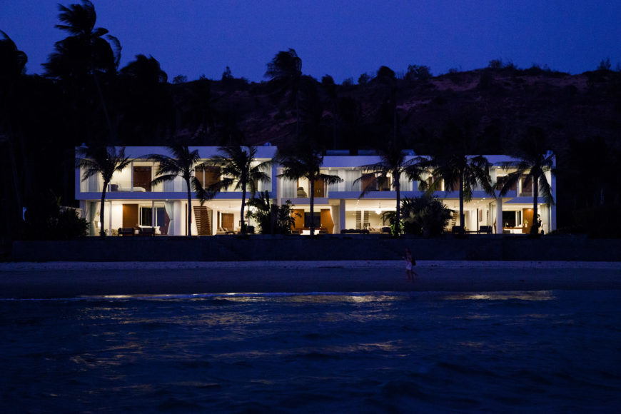 The entire property as seen from on the water itself, glowing at night time behind a row of palms.