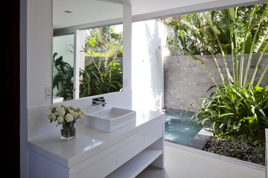 Inside the bathroom looking out toward the private jacuzzi, we see the marble topped vanity with rectangular vessel sink.