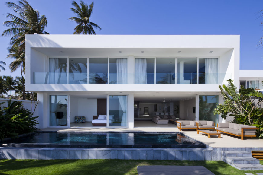 Head on view of the home from beach side. Dark tile within the infinity pools draws contrast with the bright patio and matches the window reflections from this angle.