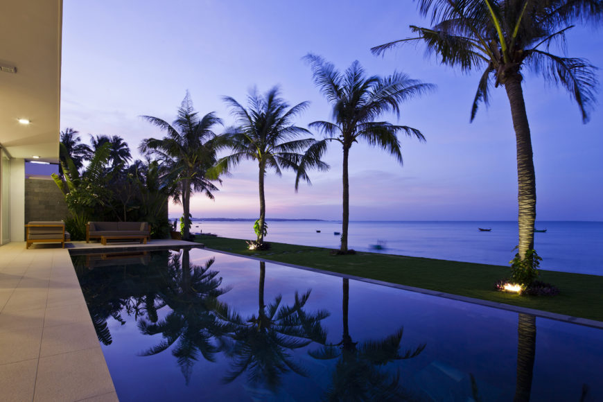 Angled view over one of the infinity pools, showcasing the calm reflection of ocean and palms alike.
