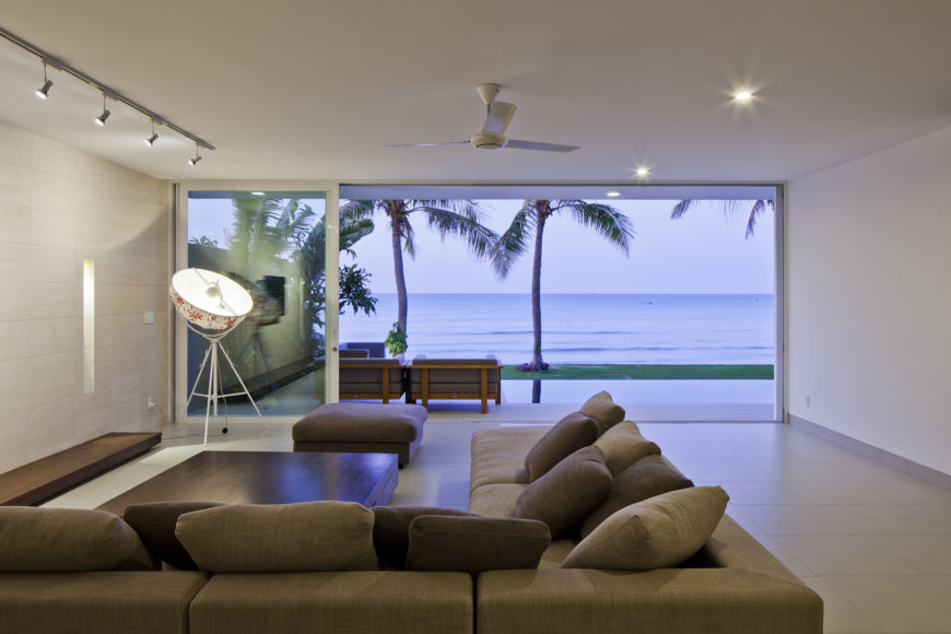 Now looking out toward the ocean, we see a unique lighting detail: the photographer's umbrella light source on left, helping brightly illuminate this open space, extending toward the wood framed patio furniture just outside.