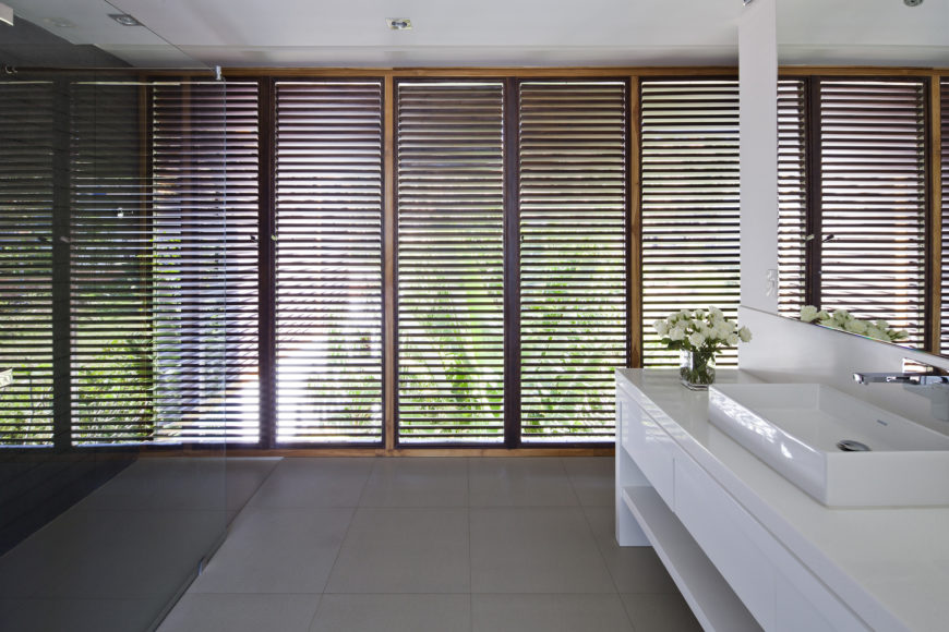 The combination of privacy and natural light afforded by the louvers makes an essential component of the upper level bathroom, featuring glossy white cabinetry and vessel sink.