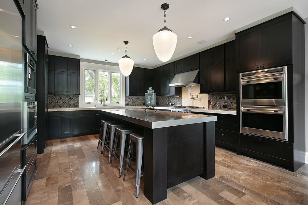 black and stainless kitchen the black is offset with stainless steel throughout including a stainless steel island countertop and stools