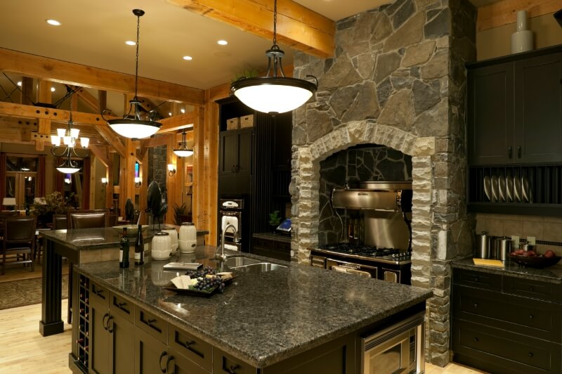 Rustic kitchen with black cabinets along with stonework