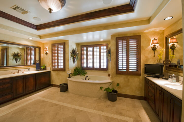 Massive expanse of beige tile flooring throughout this high ceiling bathroom stands between matching wall-width vanities in dark wood, with white marble countertops and large soaking tub at center.