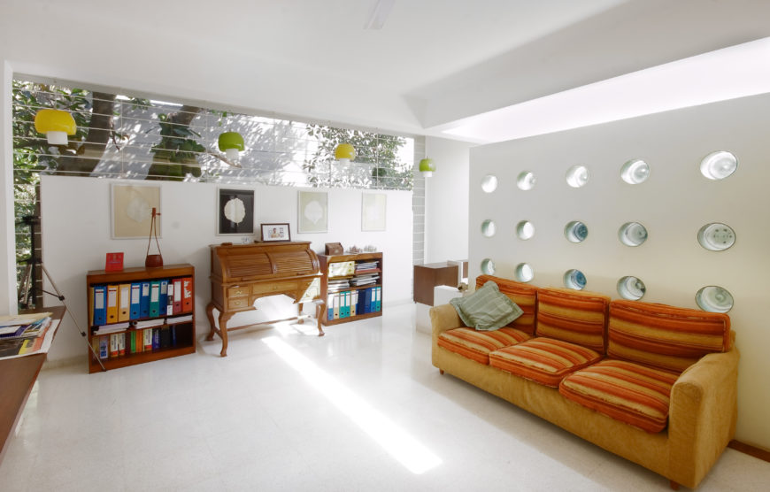 Upper level room featuring bright splashes of color, breaking up the natural wood on white theme. Orange sofa pairs with wood roll-top desk beneath multi-colored dome chandeliers, before expanse of upper wall exterior glass.