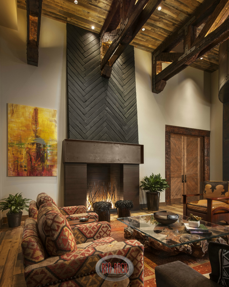 soaring ceiling with exposed wood beams cap this rustic living room with a distressed wood floor - Rustic Interior Design Ideas