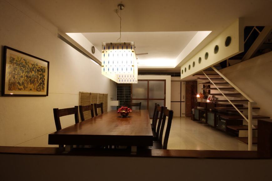 Main dining room features lengthy natural wood table beneath large, patterned cube chandelier. Floating stairs on right conceal dark wood cabinetry beneath.