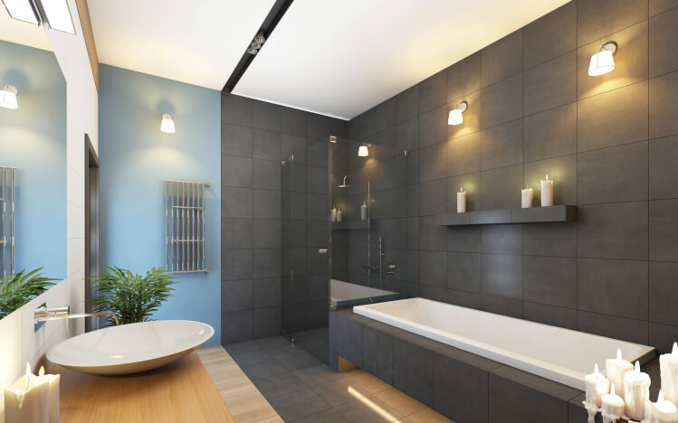 A wide range of color defines this bathroom, holding two distinct halves. Left side features blue wall, light wood flooring, and natural wood vanity with wide vessel sink, hwile right side is awash in dark grey tile, surrounding a lengthy soaking tub and glass shower.