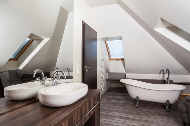 Here's another bathroom contrasting bold white sloped ceiling with dark natural wood flooring. Vanity is in a lighter tone, with vessel sink, standing across from traditional claw foot tub.