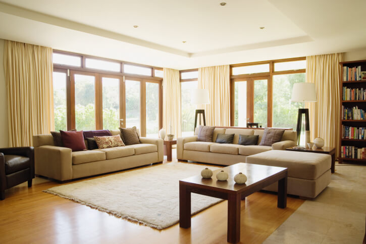 Light Hardwood Flooring Matches Exterior Glass Wall Frames In This Neutral Toned Living Room Awash