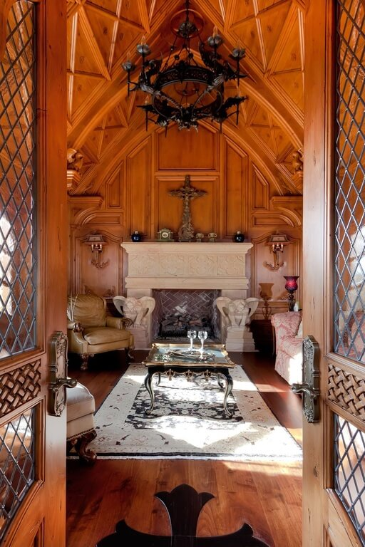 This narrow living room packs a large carved fireplace with gargoyles on either side. A white and black rug covers the warm wood floor and draws the eye towards the fireplace. The walls and vaulted ceiling are all wood.