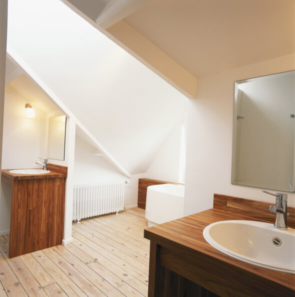 This bathroom features a pair of natural wood vanities with white sinks, flanking a separate bath space beneath a sloped ceiling with skylight over light hardwood flooring.