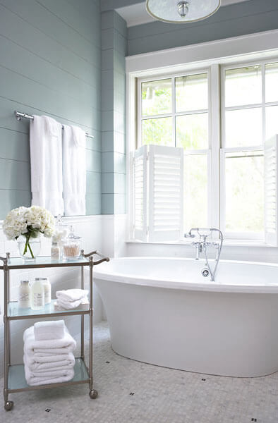 Master bath in tranquil shades of white, tan, and aquamarine, holds this deep white pedestal tub over patterned tile flooring.