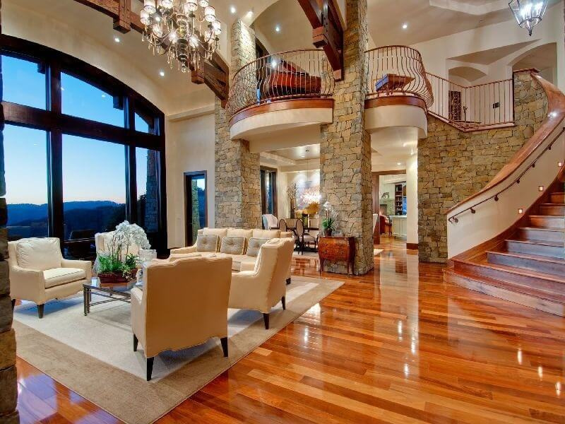 this two story living room is over looked by a balcony between two stone - Hardwood Floors Living Room