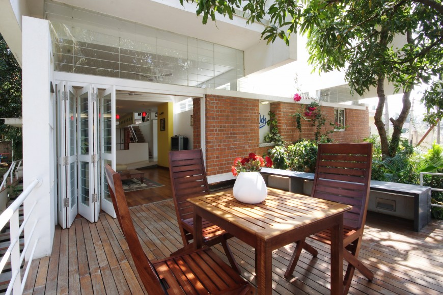 Wood patio on the front, left section of the home features matching natural wood dining set, with hinged glass panels opening a full wall to the main living space inside.