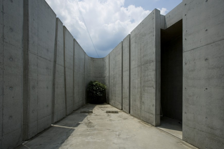 exterior wall bends sharply at the corners with greenery placed strategically throughout the outside space - Design Of Reinforced Concrete Walls