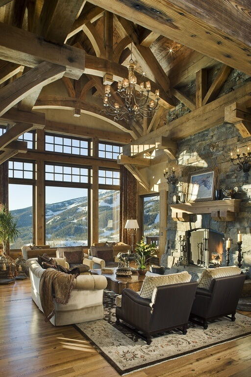 Arched wooden ceilings with exposed beams come down into a large stone fireplace covered by a screen. Light hardwood floors are covered with a beige and brown patterned rug. Mix and matched textures and materials  add visual interest.