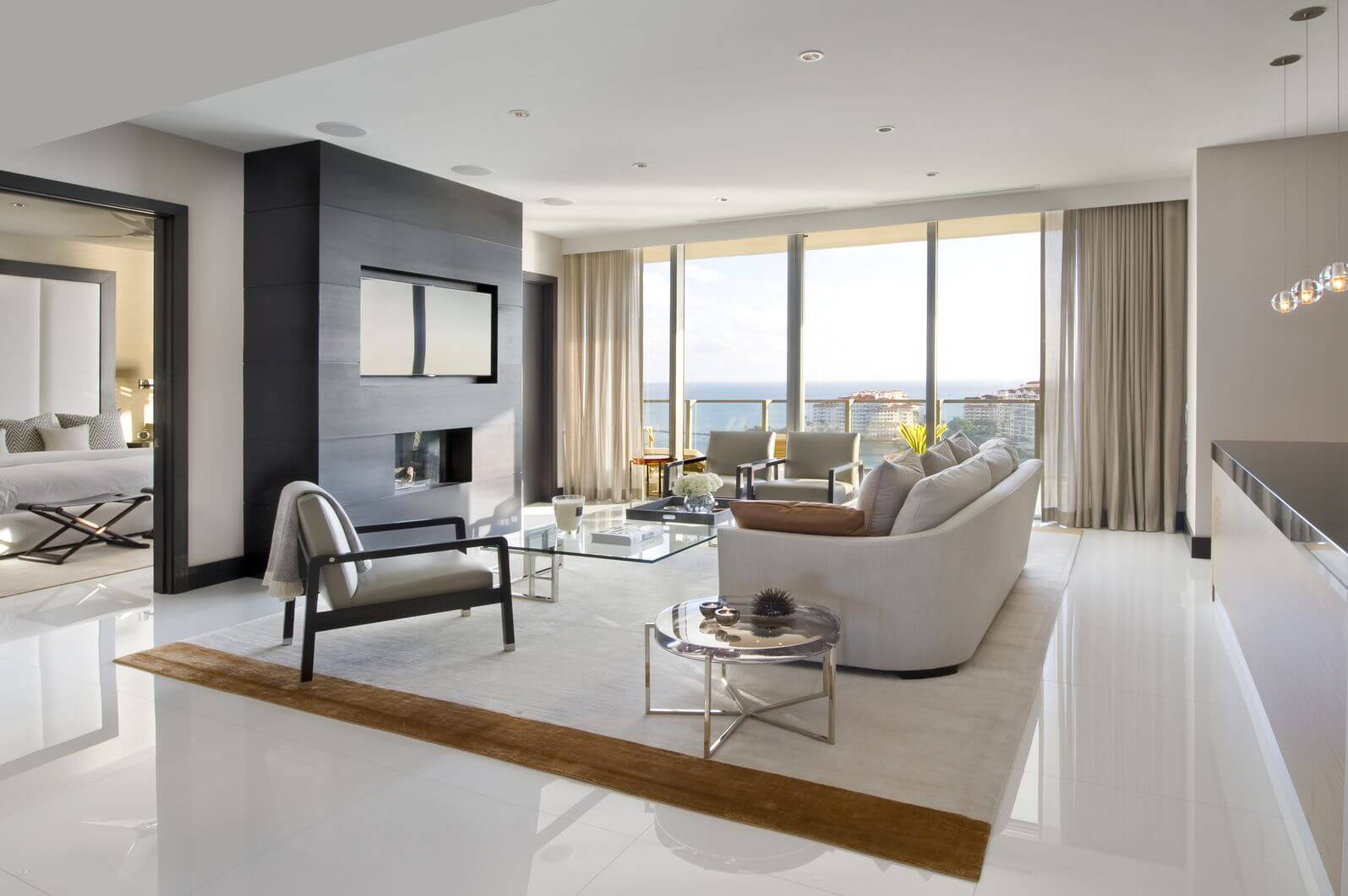 A modern living room with glossy white floors warmed up with a white and  brown rug