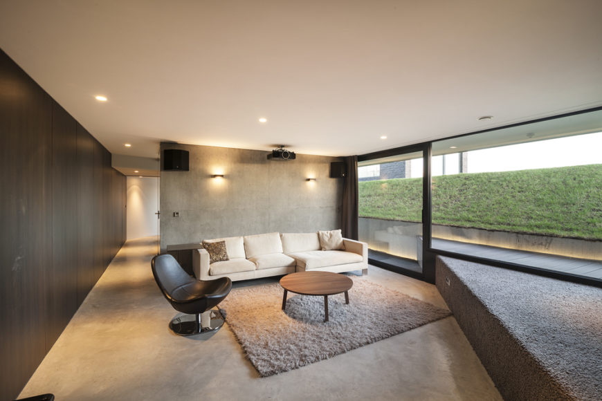 Lower level cinema room features white sectional, bucket style chair and natural wood table over shag rug, with view up the sloping lawn to the right.