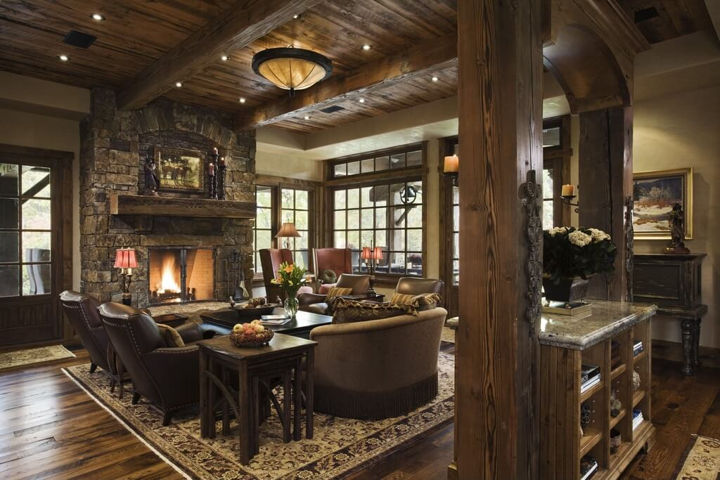 A large stone fireplace and a seating area with four leather chairs and a loveseat dominate the majority of this living room. A smaller seating area with two red arm chairs is in the corner near the windows.