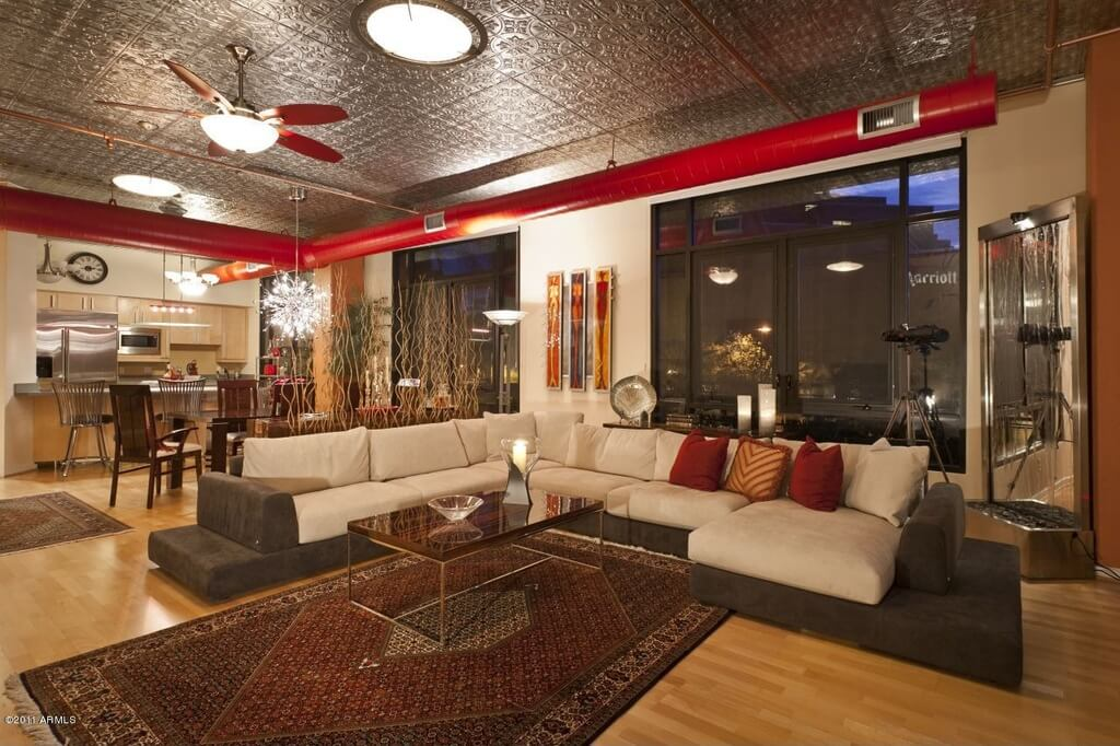Bright red exposed vents criss-cross the textured metal ceiling of this red and beige living room. A fountain in the corner provides ambient noise.