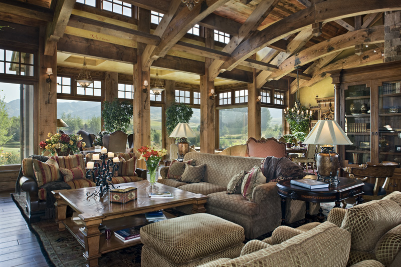 rustic styled living room spreads a lavish variety of sofas and rich wood furniture below a - Wooden Living Room