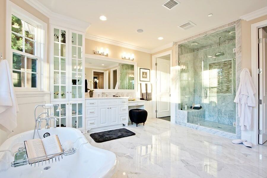 marble flooring anchors this bright bathroom featuring full height glass door cabinets next to a - Master Bathroom