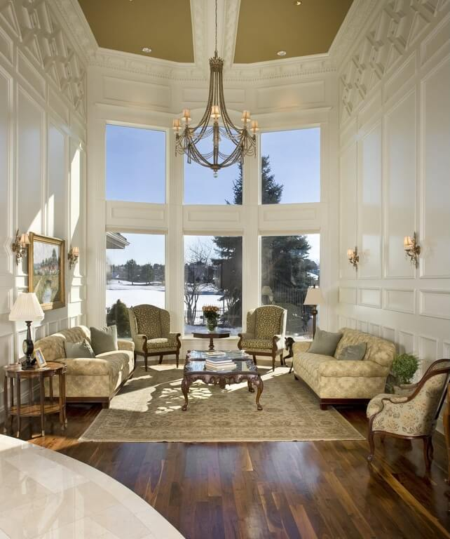 Intricately detailed ceiling and walls flow down to mixed dark and light wooden floor.  Chairs and sofas in various patters of cream and olive surround a glass-topped coffee table.