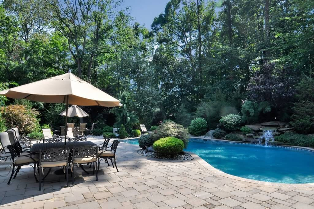 Pool and patio at the edge of a small forested areas. Pools with trees and bushes as a backdrop is almost as beautiful as infinity pools on the edge of a cliff.