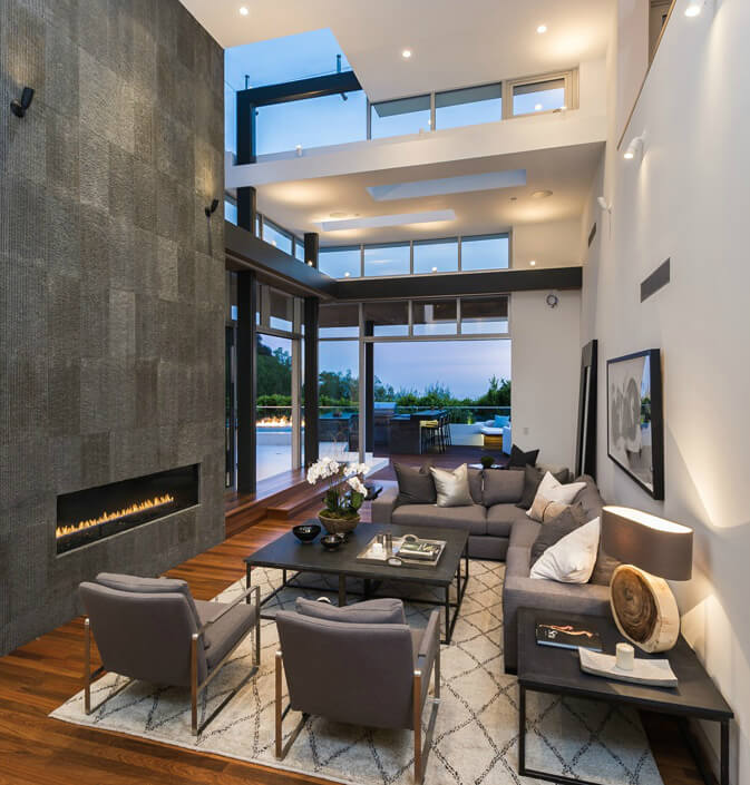 Two Story Living Room Stands Lush Hardwood Flooring And Muted Grey Contemporary Seating Next To An