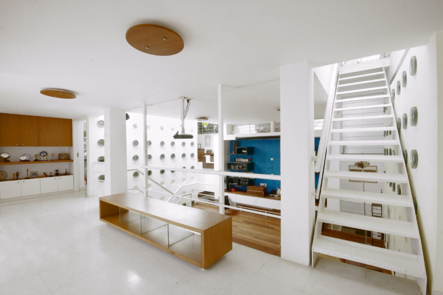 View overlooking the central living space, revealing separate staircases leading to each of the twin upper structures. Mixture of white tile and minimalist, natural wood textures defines the look.