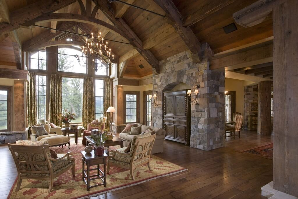 Wood and stone construction allows for soaring ceilings and large arched windows. Floral curtains and patterned seating give the room a softer feel.