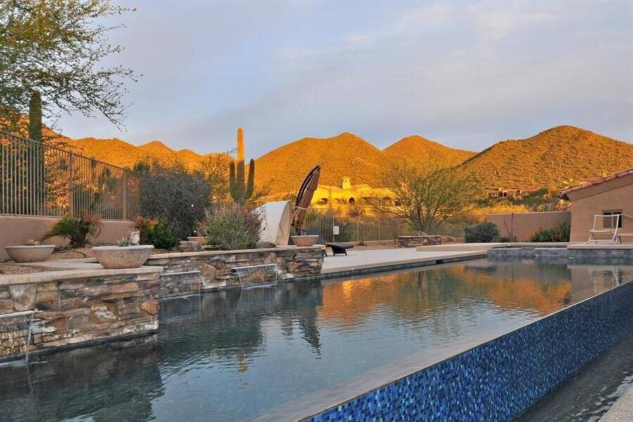 Here's another beautiful pool (infinity style) in the backyard of a desert home. This is a long and large pool with a tiered surrounding patio. The surrounding fence is made up of vertical bars which enables you to see the stunning desert vista.