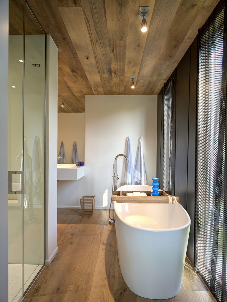 """White pedestal tub sits next to perforated metal exterior wall shade in master bath, fearing glass door walk-in shower and another """"floating"""" white slab countertop."""