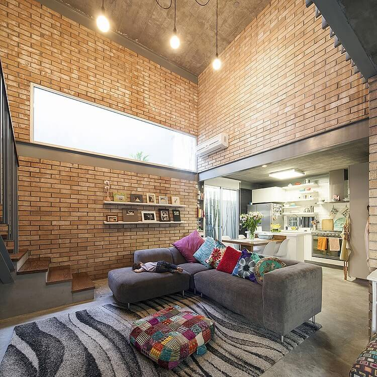 The central living room space reaches two stories high, with brick walls surrounding the metal structure on all walls. L-shaped sectional with variety of throw pillows stands next to multicolored ottoman, with kitchen and dining space in background.