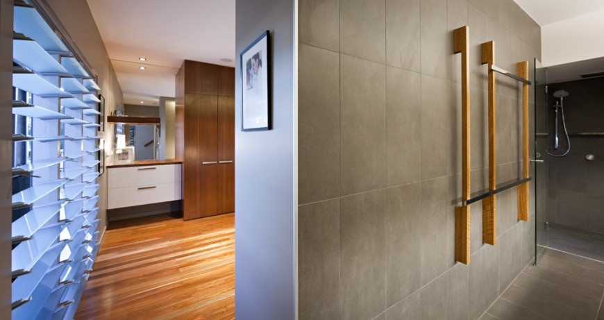 Bathroom opens directly from bedroom, with grey tiling throughout and unique wood and metal rails on wall before glass door shower.