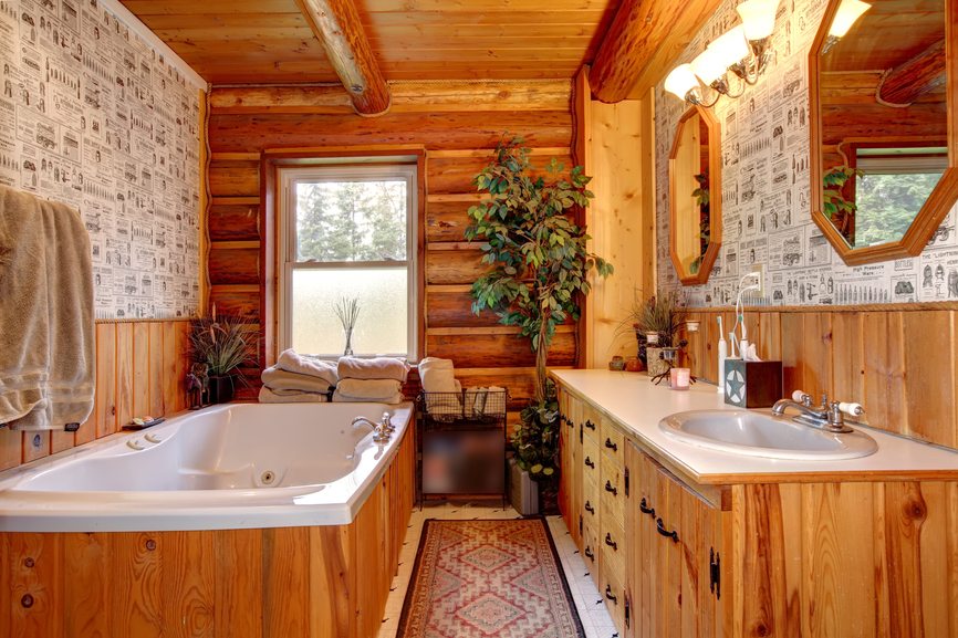Unique rustic look bathroom features natural wood vanity and lower walls, bathtub frame, and log style exterior wall and ceiling.