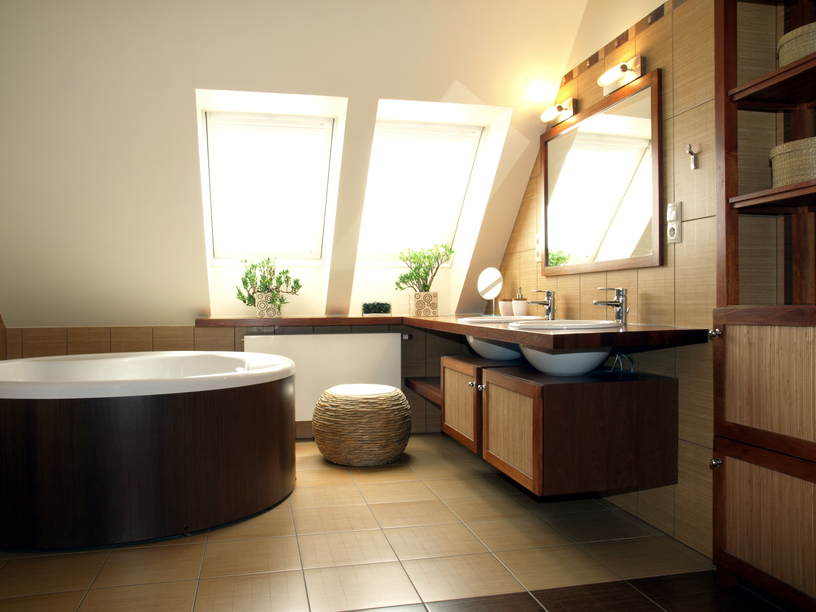 Zen-inspired minimalist bathroom features free standing soaking tub wrapped in dark wood, with floating countertop and lower cupboards in matching wood, with beige and brown tiling all around.