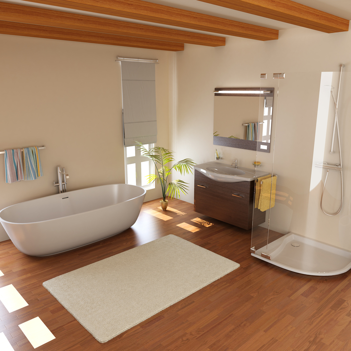 Lush modern bathroom features natural hardwood flooring, dark wood floating vanity, large pedestal tub and curved glass shower in minimal, white room with exposed wood beams.