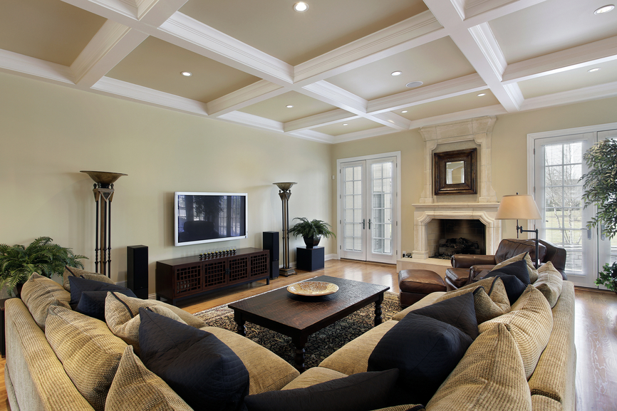 White beam detailed ceiling stands over this beige and natural wood toned living room, featuring immense L-shaped sectional and leather armchair. Dark wood coffee table and entertainment cabinet add contrast with white marble fireplace.