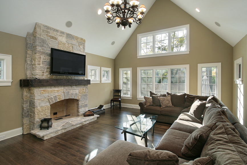 Vaulted Ceiling And Sculpted Metal Chandelier Hang Above A Wide Expanse Of  Plush Cushioned Brown Sectional