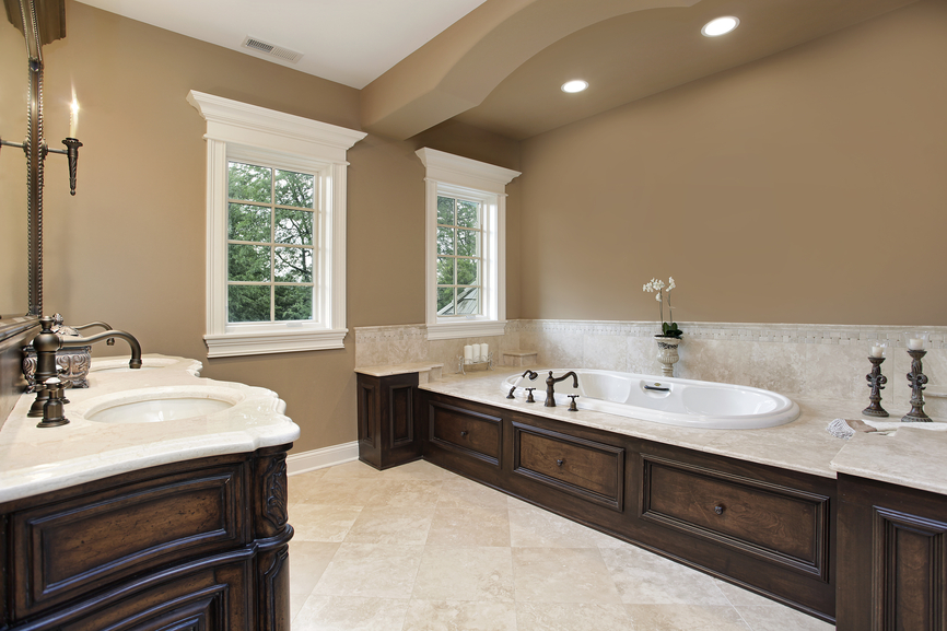Large, open light brown toned bathroom features expansive marble topped, dark wood soaking tub surround, standing across beige tile flooring from matching carved wood vanity with white marble countertop.