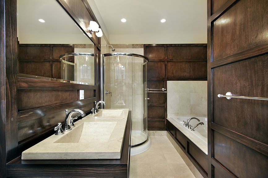 This master bath contrasts between lush, dark wood paneling on walls and vanity, and white marble sinks, flooring, and bathtub surround. Circular glass shower stands in corner with more beige tile.