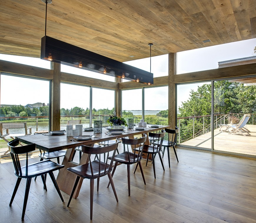 The major open space forming the body of the interior includes this sunlit dining area, with overhead metal lighting rack hung above lengthy wood dining table. Sliding glass doors all around are framed with large natural wood beams in the exterior structure.