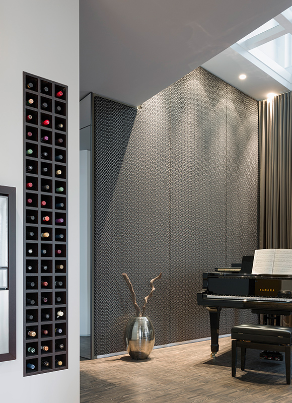Grand piano stands in living room over dark stained oak parquet flooring, with black wood wine rack built into wall at left.