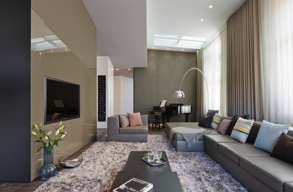 l breadth of the living room highlights lengthy brown sectional, enormous shag area rug, and minimalist textures across all surfaces. Glossy brown media wall on left, tiny embedded lights in ceiling, and shimmering, full height curtains tie the room together.